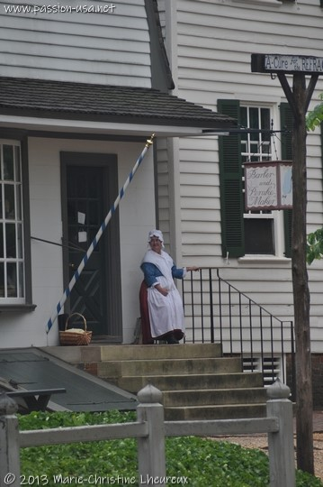 Colonial Williamsburg, costumed actress in front of the barbershop